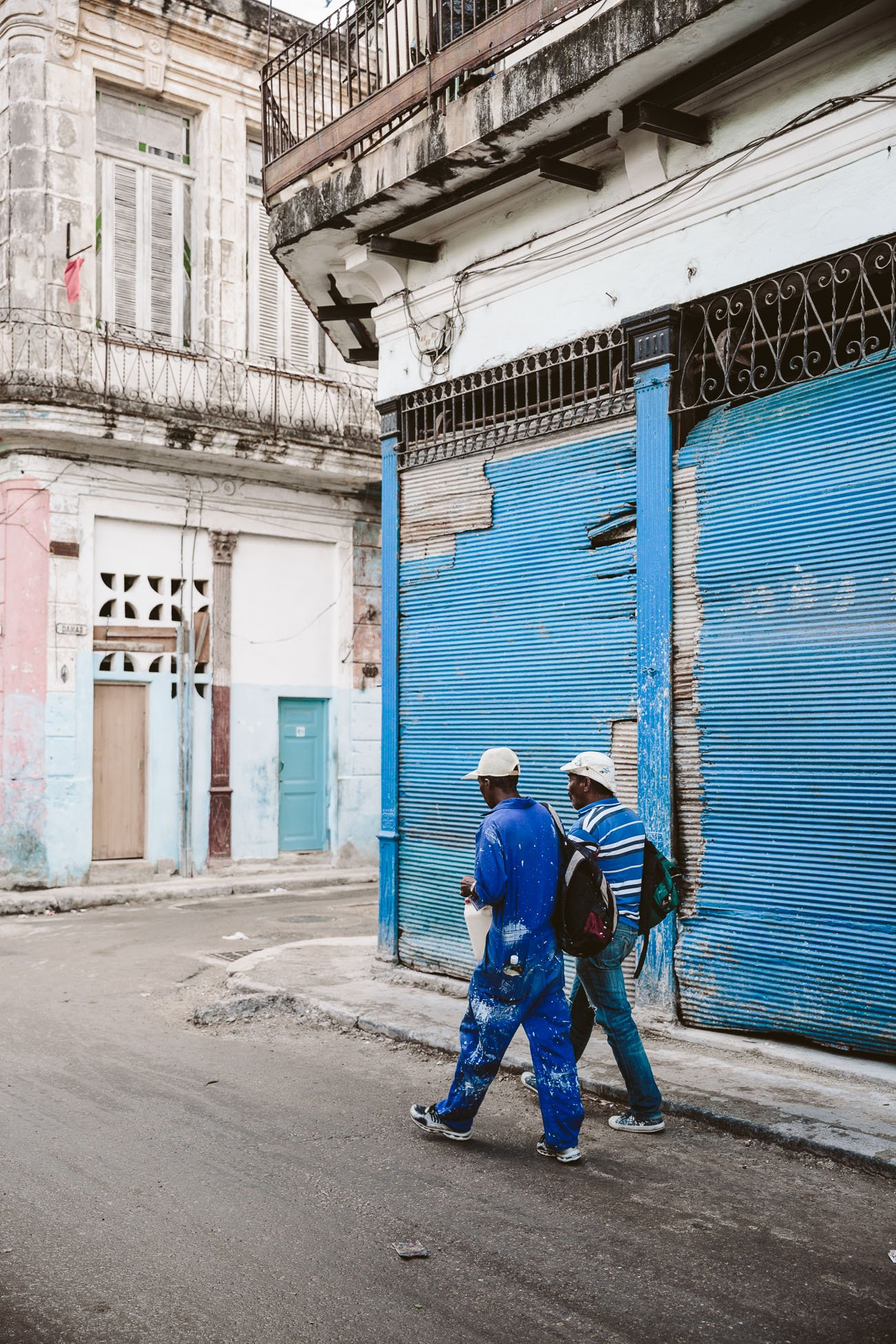 Workers dressed in blue walk by a blue door in Havana Cuba