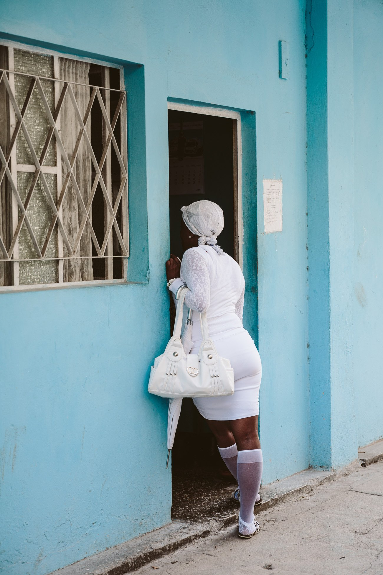 Girl dressed in white standing in street in Havana Cuba